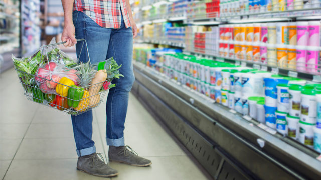 person standing in grocery aisle, holding a basket of produce