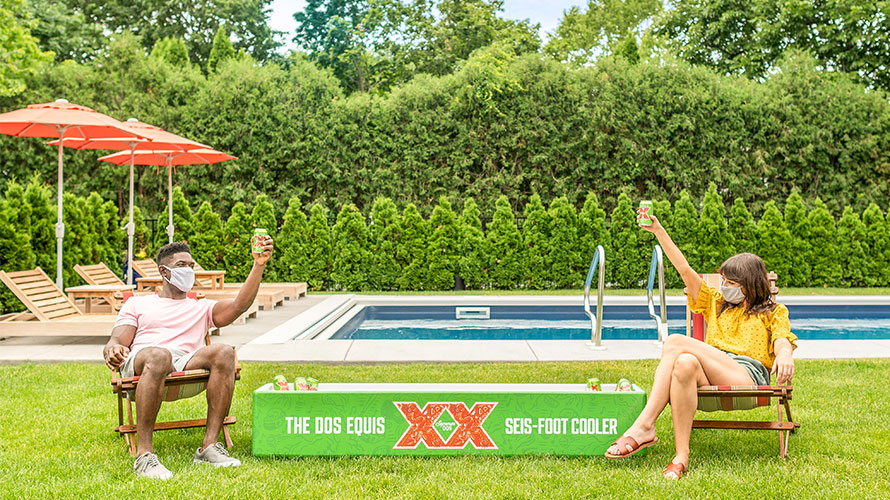 Photo of the Dos Equis seis-foot cooler with two people giving cheers