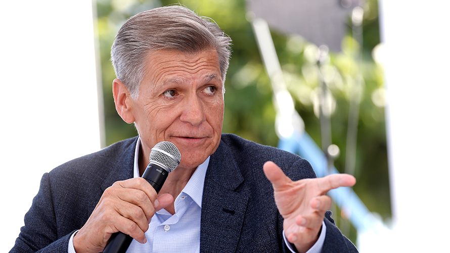an older white man speaking into a microphone and gesturing with his other hand
