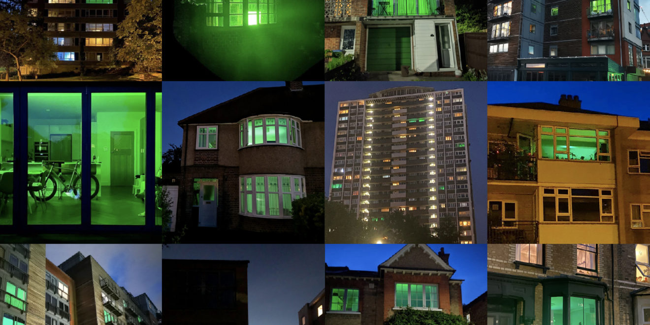 squares of different building with green lights shining out the windows
