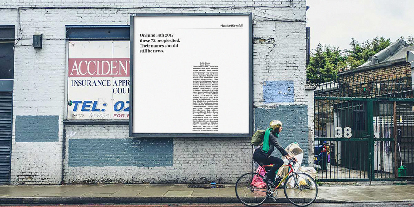 someone biking past a billboard that has text shaped like a building