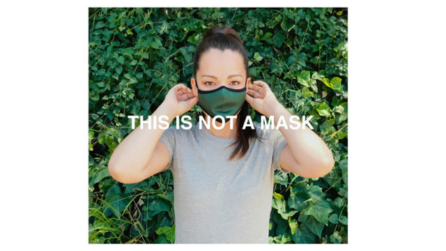 A woman wearing a mask with text that says,