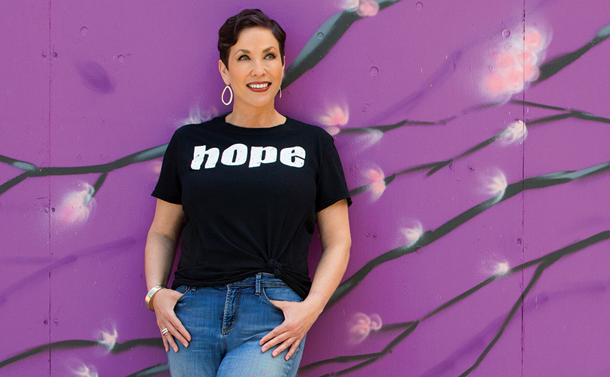 a woman with short brown hair wearing a shirt that says hope, leaning against a purple wall