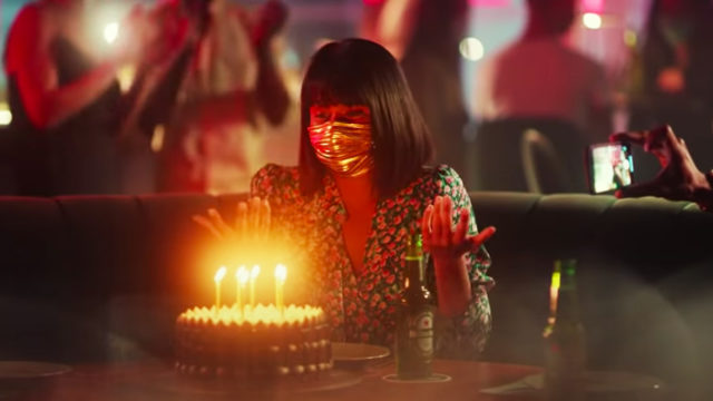 Woman wearing a mask with a birthday cake