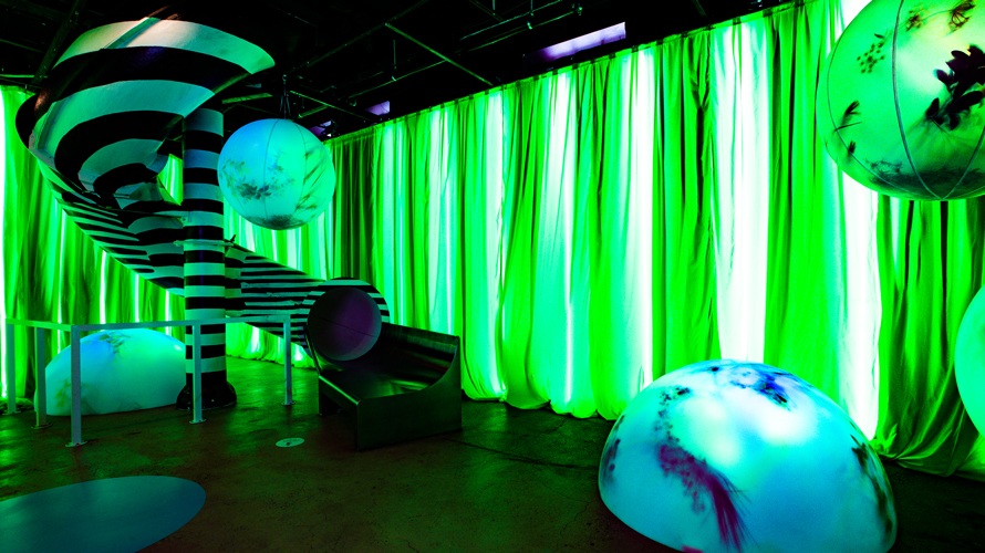 neon green lit walls with a curved slide