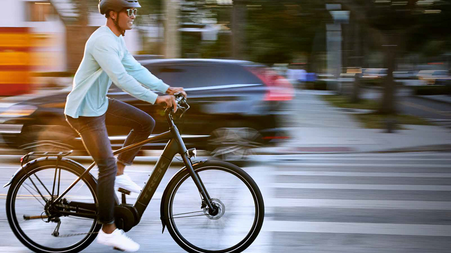 a man riding a bike with a car blurred in the background