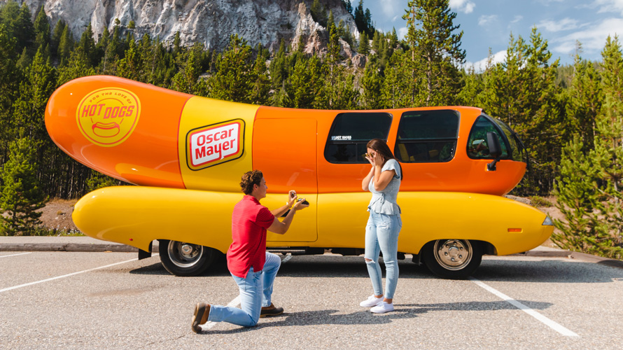 Man proposing to a woman in front of a Oscar Mayer Wienermobile