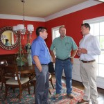 Bluegrass Energy representatives Barry Drury and Jeff Moberly speak Thursday with Alex Carter, a HERS rater, after a press conference by the Home Builders Association of Lexington.