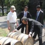 Y.J. Choi attempts to lift a barrel of bourbon at Woodford Reserve during his visit to Kentucky. The ambassador of the Republic of Korea to the United States spoke at Kentucky World Trade in Lexington.
