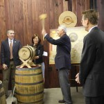 Gov. Steve Beshear hammers the bung into a commemorative barrel at the press conference announcing a new tourism adventure that links the state's micro-distilleries.