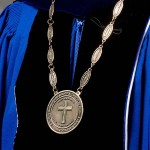 A medallion inscribed with the Berea College seal is suspended from a chain bearing the names of previous Berea College presidents and key words from the college's Great Commitments.