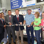 Kentucky Agriculture Commissioner James Comer, third from left, Walmart regional buyer and market manager Tino Soto, left, cut the ribbon on Udderly Kentucky. They are accompanies by representatives from Kentucky dairy farms and Prairie Farms, the facility that will process the milk.