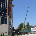 Officials celebrate the opening of Central Hall I and II as workers construct another new residence hall next door.