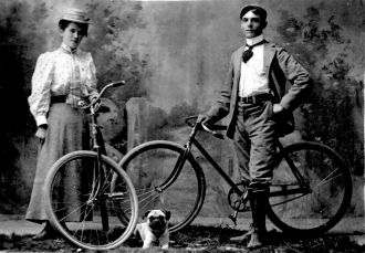 Young couple on bikes, 1900