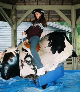 girl rides black white mechanical bull