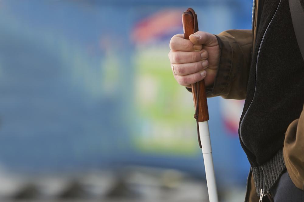 Imagem de um deficiente visual segurando um bastão guia
