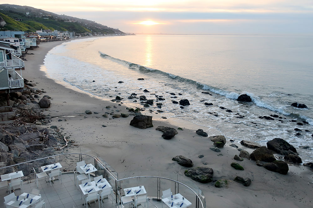 A view of the beach and the restaurant terrace from our King Premier Ocean Front room at the Malibu Beach Inn