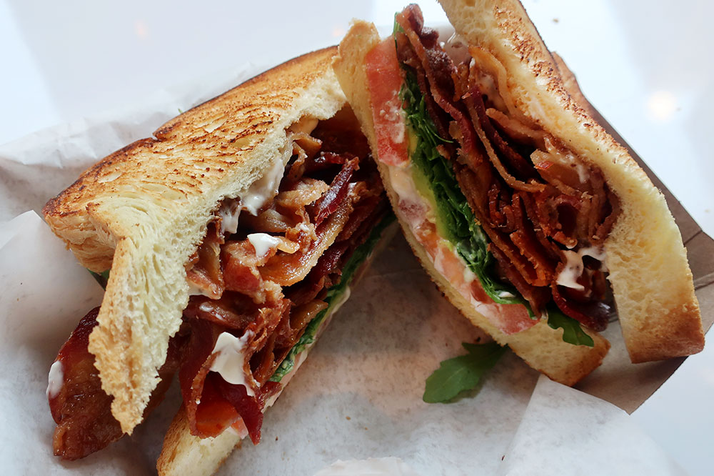 A BLT with bacon, arugula, tomato, avocado and truffle aioli on toasted challah from The Fat Shallot at Revival Food Hall in Chicago