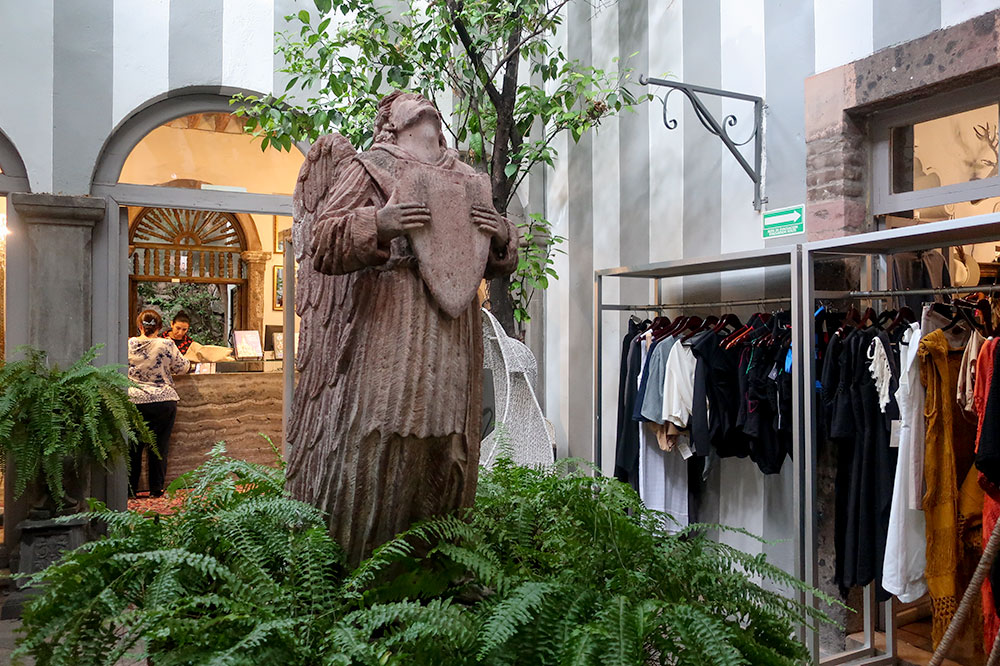 Stone sculpture of an angel in the central hall of Casa R Concept Store