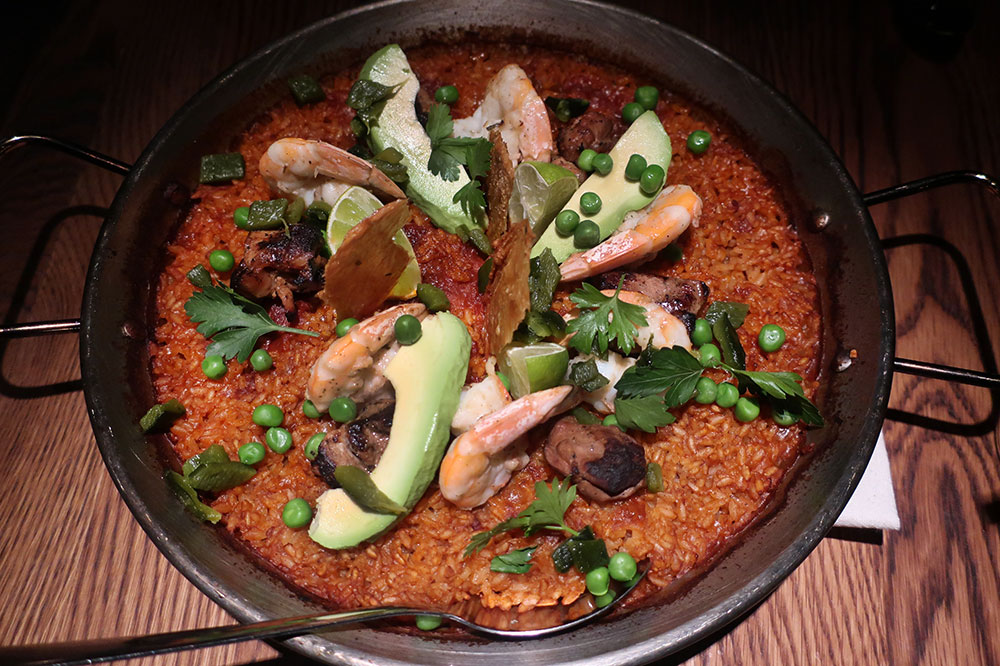 Mexican paella with Gulf shrimp, Gunthorp Farms chicken thighs, red chile adobo, roasted poblano pepper, tomato, peas, avocado and chicken chicharrón from Bar Sótano