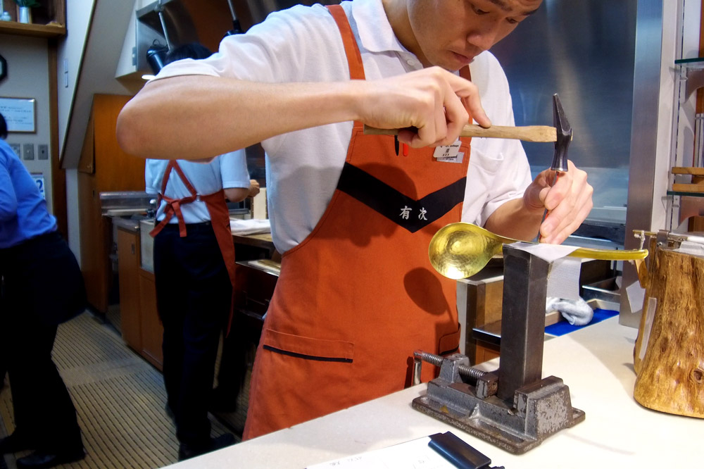 An engraver personalizing a brass ladle at Aritsugu in Nishiki Market - Photo by Hideaway Report editor