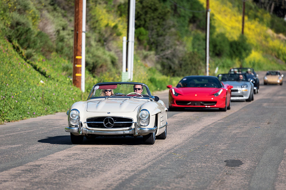 A white 1959 Mercedes-Benz 300SL Roadster followed by a red Ferrari 458 Italia and a rare silver BMW Z-8 at the La Jolla Concours d'Elegance in La Jolla, California
