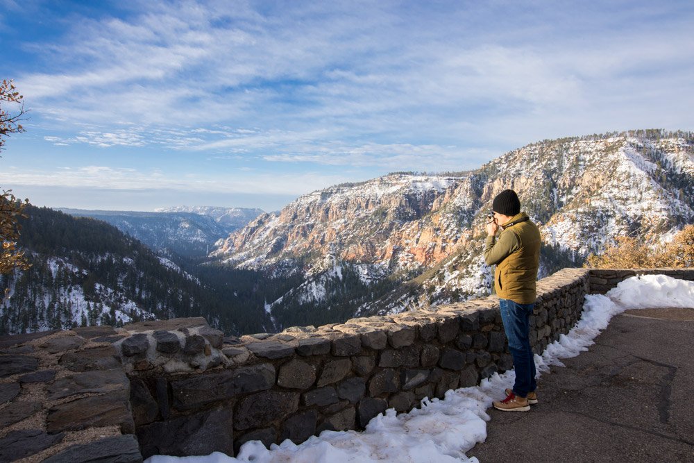 A visitor stopping to photograph Oak Creek Canyon near Flagstaff, Arizona, en route to Utah