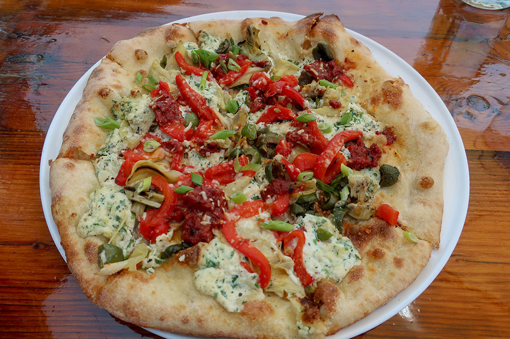Pizza topped with roasted tomato sauce, pecorino, garlic ricotta, roasted artichoke, red pepper, scallion and Castelvetrano olives at Silver Star Café