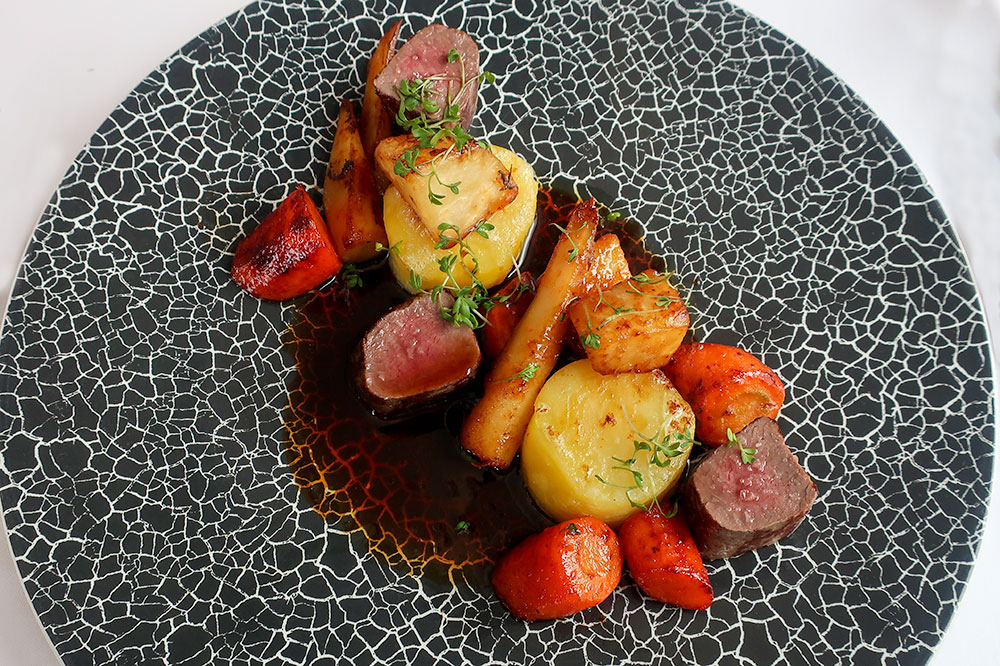 Venison saddle in a venison demi-glace with potato fondant and glazed parsnips, carrots and turnips at Pavillon in Brno