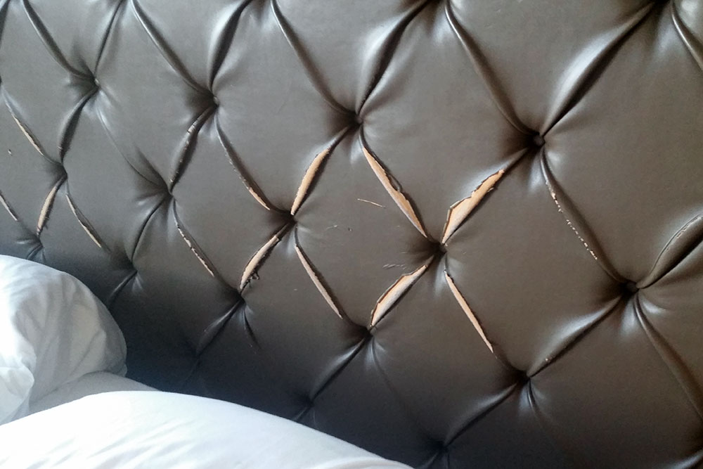 Frayed leather headboard of our bed at Fairmont Heritage Place
