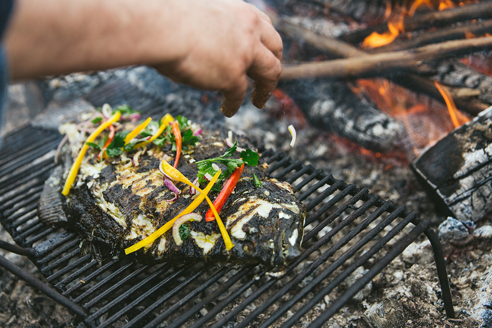 Whole fish being cooked over embers