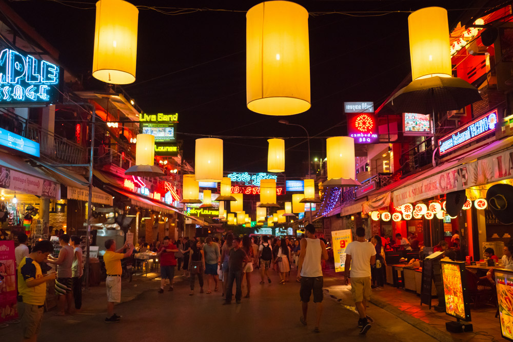 Backpackers and tourists walking along the illuminated Pub Street in Siem Reap, Cambodia