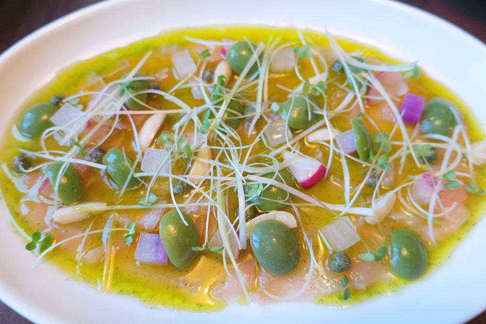 Albacore tuna crudo at <em>Kissa Tanto</em>, garnished with olives, Tokyo leeks and capers, in olive oil and a shiso vinaigrette