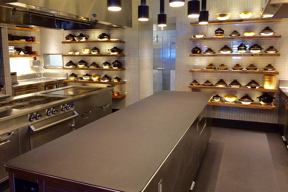 The open kitchen with donabe, the classic Japanese ceramic cooking pots, on the shelves