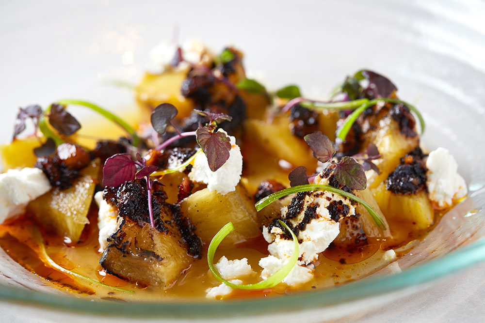 Roasted pineapple with pungent goat cheese, tangy orange-lime broth and hazelnut salsa macha at <em>Leña Brava</em>