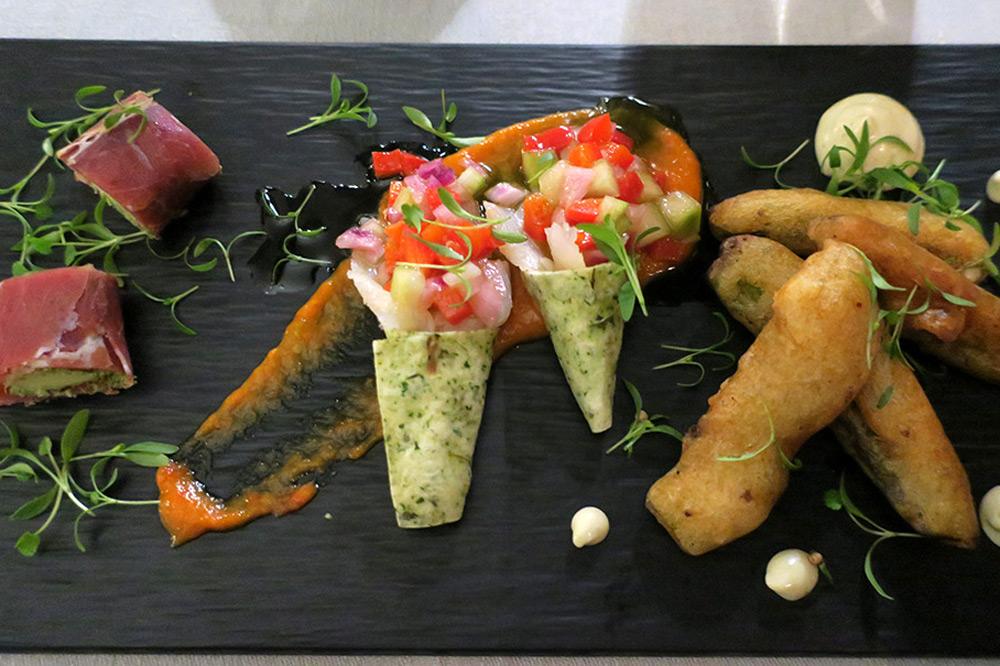Portuguese tapas (from left: pata negra ham wrapping Azorean Ilha cheese and parsley pesto, cones of smoked cod, and sugar-pea tempura) at <em>Sítio</em> restaurant at the Valverde Hotel
