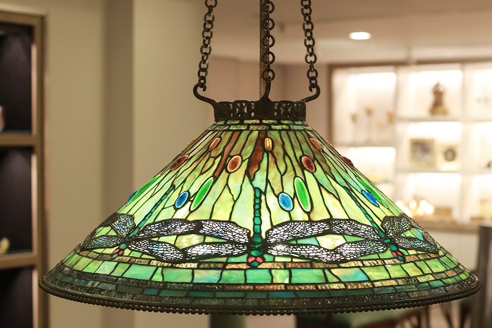 A Tiffany Studios Dragonfly glass-and-bronze lamp displayed at Macklowe Gallery