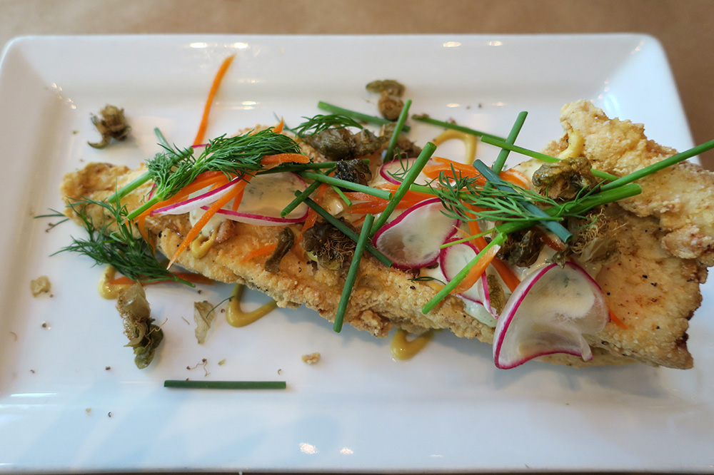 Chicken-fried trout with fried caper flowers, radish slices, chives and pickled carrots from <em>Little Bird</em> in Portland, Oregon - Photo by Andrew Harper