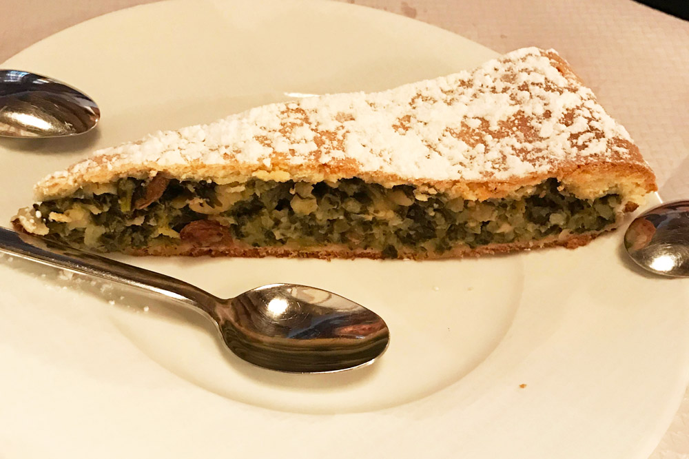 A tart bathed in powdered sugar and stuffed with a sweet-savory filling of Swiss chard and pine nuts at <em>La Merenda</em>