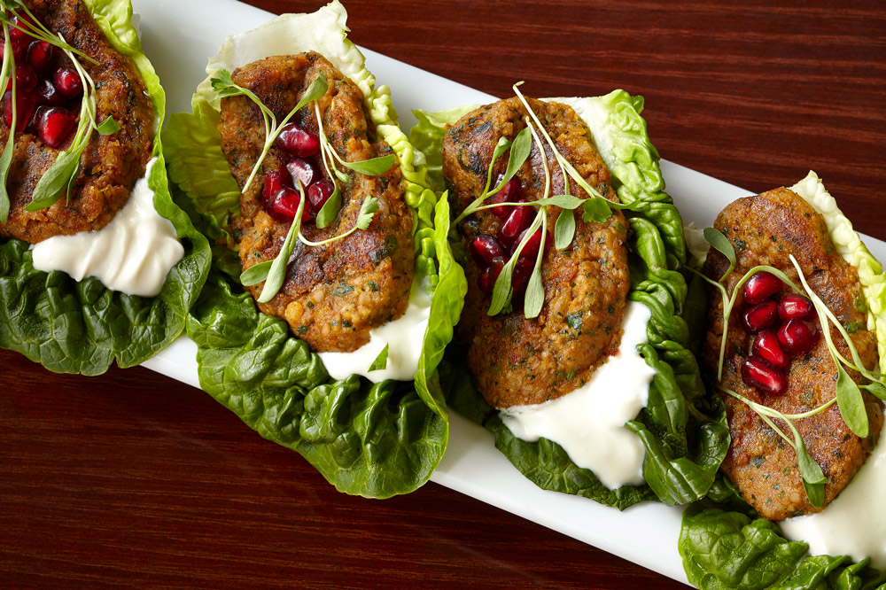<em>Mercimek Köftesi</em>, traditional seared red lentil patties, preserved lemon yogurt, pomegranate, lettuce leaves at <em>Zaytinya</em>