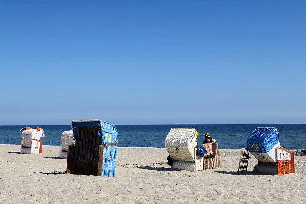 <em>Strandkörbe</em>, which are hooded basket-like chairs, lined up on the beach in Hohwacht, Germany - Photo by Andrew Harper