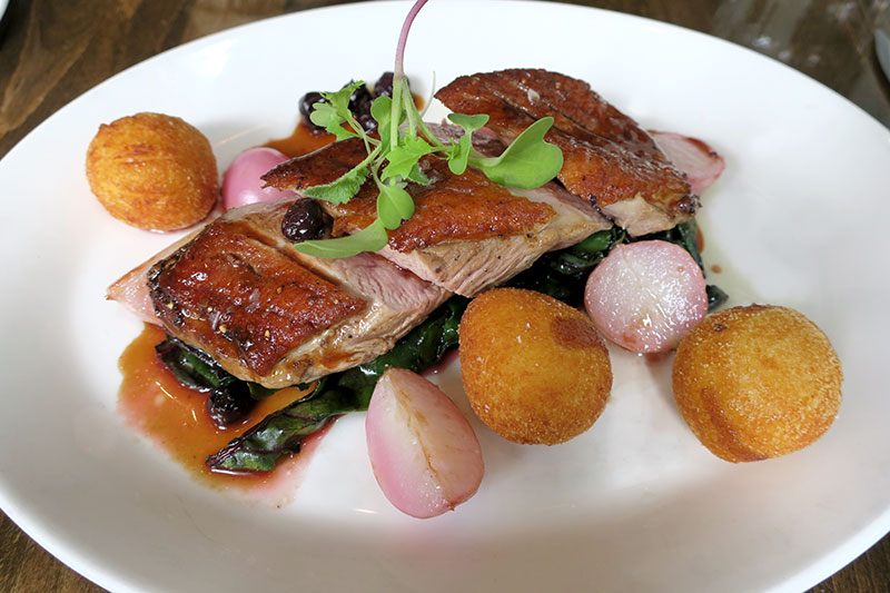 Duck breast with a blueberry-mustard jus and pommes dauphine (potato puffs) at Tableau Bar Bistro - Photo by Andrew Harper