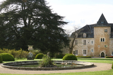 A pond in front of the exterior of Château de la Treyne in Lacave, France
