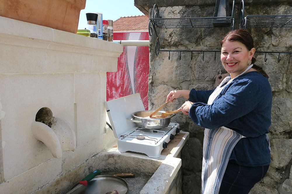 Katja at the stovetop of her outdoor kitchen in Dubrovnik, Croatia