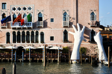 "Lorenzo Quinn's ""Support"" sculpture in the canal and the exterior of Ca' Sagredo Hotel in Venice, Italy"