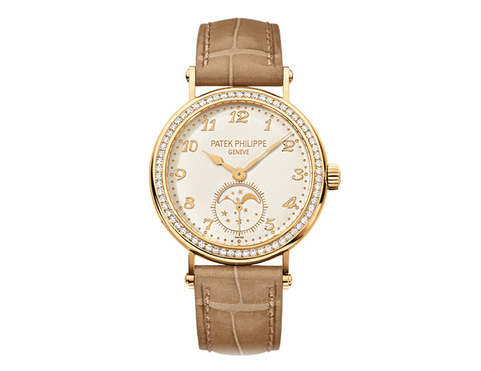 Patek Philippe Calatrava ladies 18k yellow gold mechanical manually wound diamond case strap watch featuring moon phases and seconds subdial with a grained cream dial.  (7121J-001)