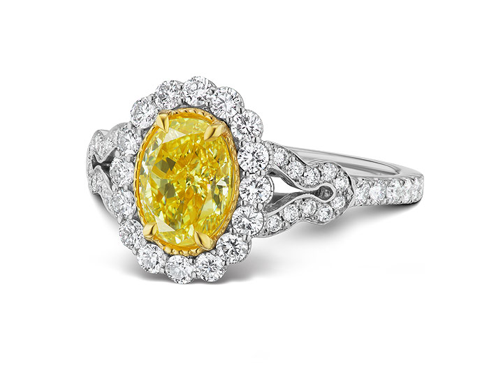 Bez Ambar oval shape natural fancy yellow diamond and round brilliant cut diamond ring in 18k white gold.