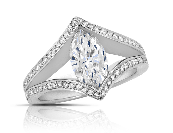 Marquise cut center diamond with round brilliant cut diamond engagement ring in platinum.