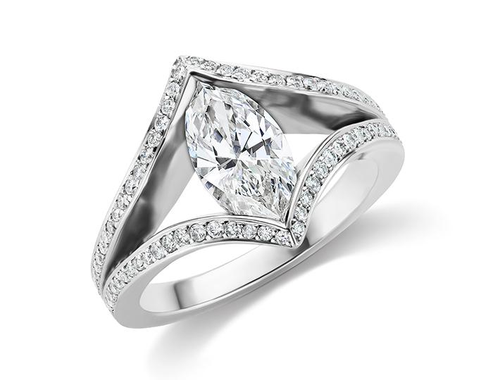 Marquise cut center diamond with round brilliant cut diamond engagement ring in platinum.