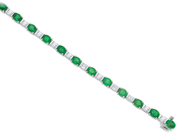 Oval emerald and baguette cut diamond bracelet in 18k white gold.